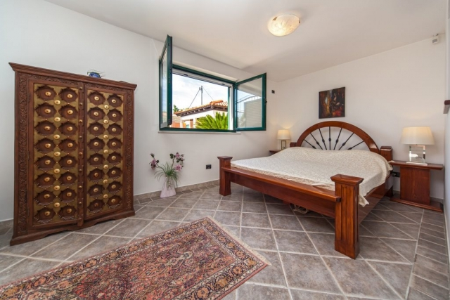 Sleeping room with a double bed with wide open window in the Villa Rasotica