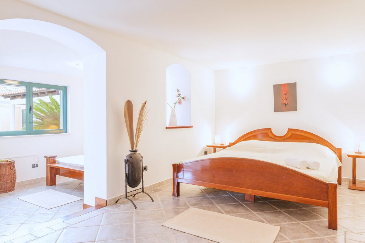 Double bedded room with single bed in minimalist bedroom in the Villa Rasotica
