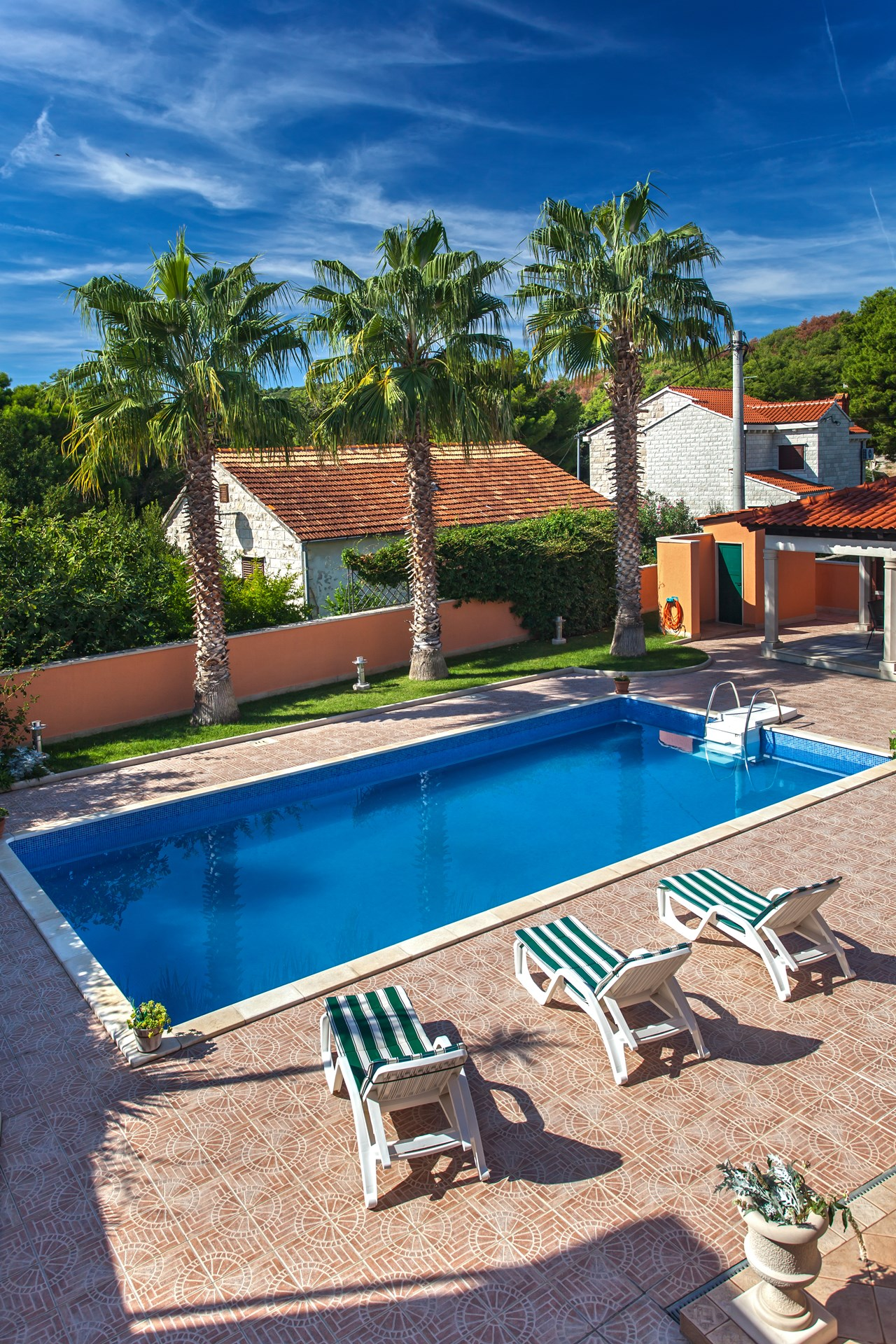Swimming pool with sunbeds and relaxing area on the front terrace the Villa Rasotica
